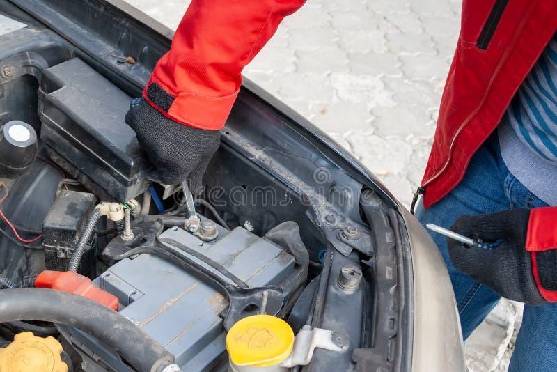 Hombre que desconecta el terminal en la batería de coche debajo de la capilla abierta de un motor de coche plano-cuatro imagenes de archivo