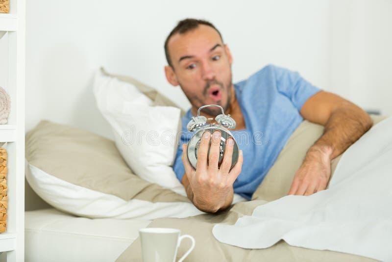 Hombre que despertaba y que realizaba él ha dormido más de la cuenta foto de archivo
