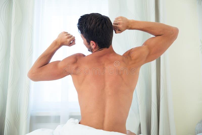 Hombre que despierta y que estira las manos imagen de archivo