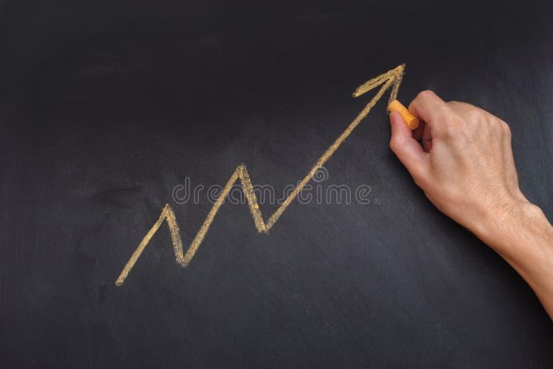 Hombre que dibuja la flecha amarilla que muestra tendencia al alza y el aumento favorables imagenes de archivo