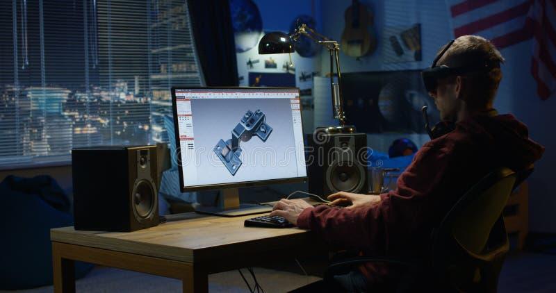 Hombre que diseña la bisagra en un ordenador fotos de archivo