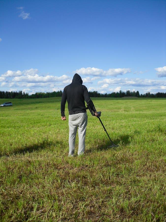 Hombre que disfruta de arqueología recreativa con el detector de metales en campo del otoño imagenes de archivo