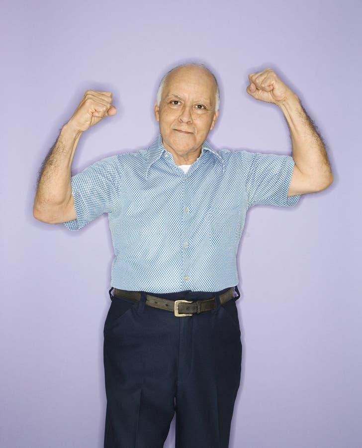 Hombre que dobla los músculos. fotos de archivo