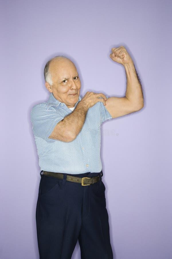 Hombre que dobla los músculos. imagen de archivo