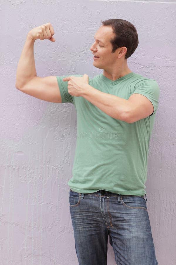 Hombre que dobla sus músculos fotografía de archivo