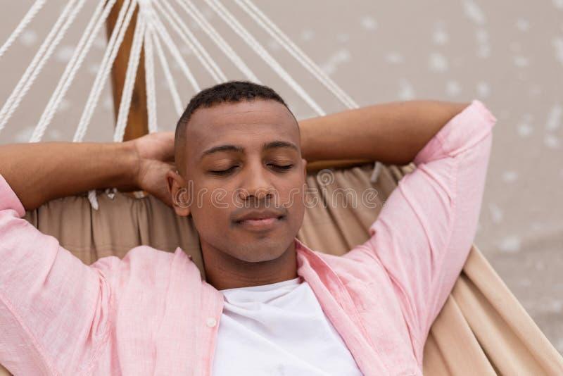 Hombre que duerme con las manos detrás de la cabeza en una hamaca fotografía de archivo