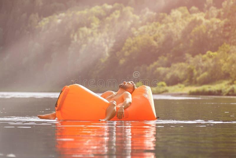 Hombre que duerme dentro de ocioso inflable en agua fotografía de archivo libre de regalías