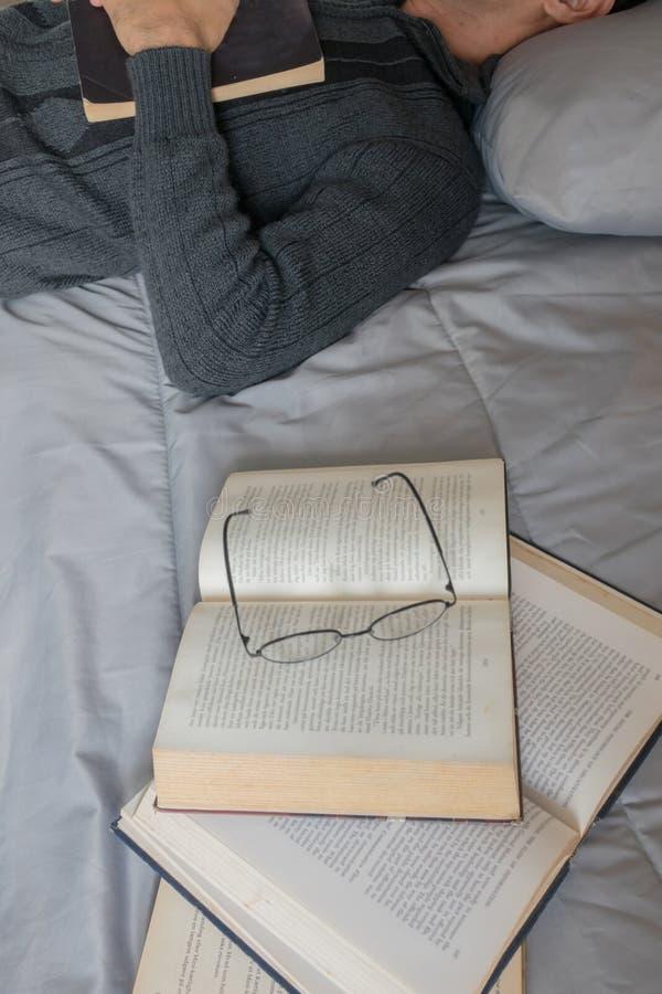 Hombre que duerme, leyendo foto de archivo