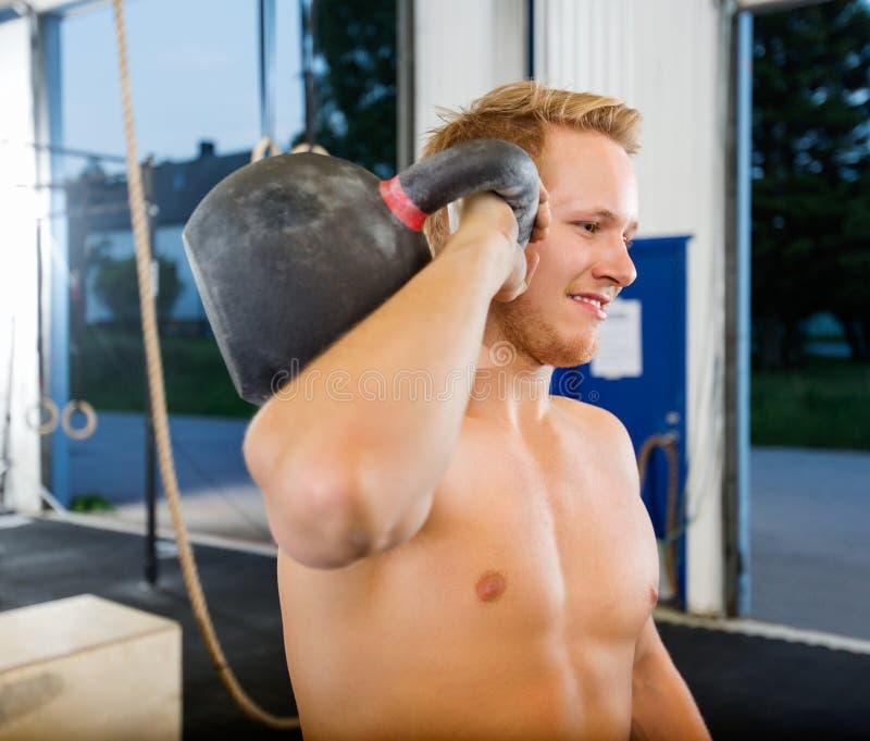 Hombre que ejercita con Kettlebell en gimnasio imagen de archivo libre de regalías