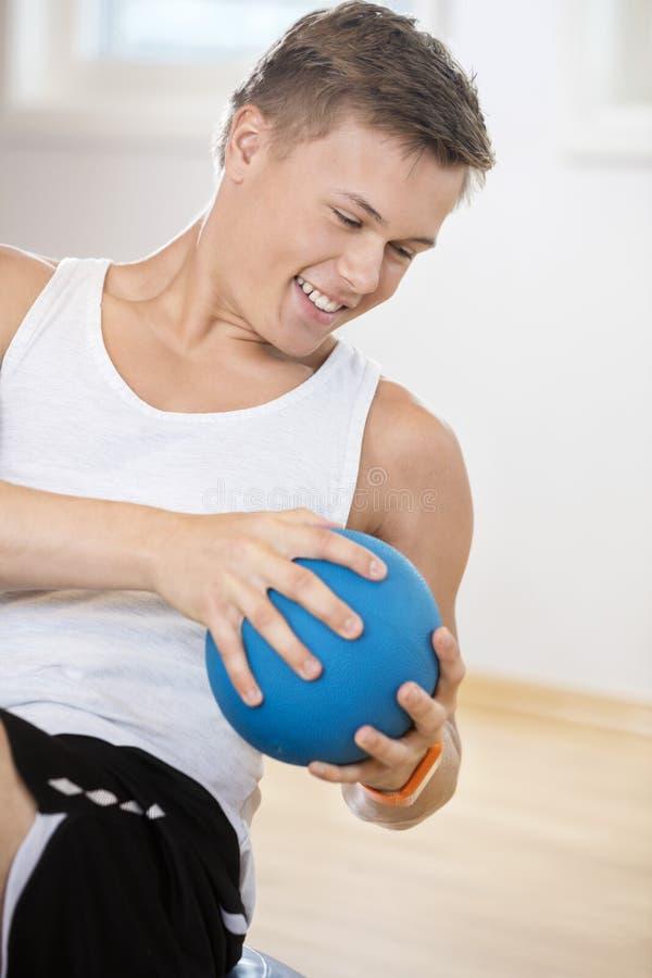 Hombre que ejercita con la bola de medicina en gimnasio imagenes de archivo