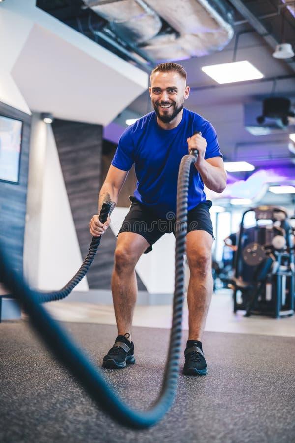Hombre que ejercita con las cuerdas en el gimnasio imagen de archivo libre de regalías