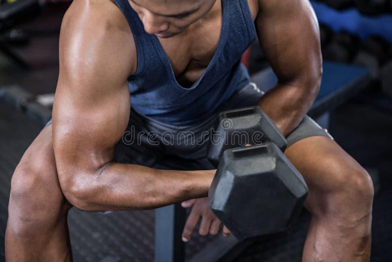Hombre que ejercita con pesa de gimnasia foto de archivo