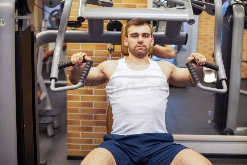 Hombre que ejercita en la gimnasia El atleta de la aptitud que hace el pecho ejercita en la máquina vertical de la prensa de banc imágenes de archivo libres de regalías