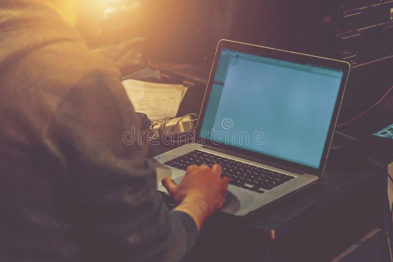 Hombre que elabora en un ordenador portátil en un cierre del sitio de la producción fotografía de archivo libre de regalías