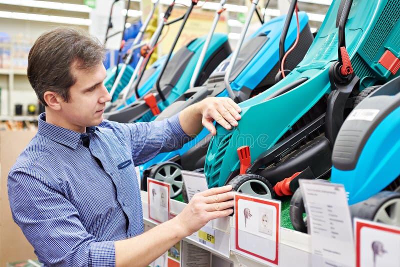 Hombre que elige los cortacéspedes en supermercado fotos de archivo libres de regalías