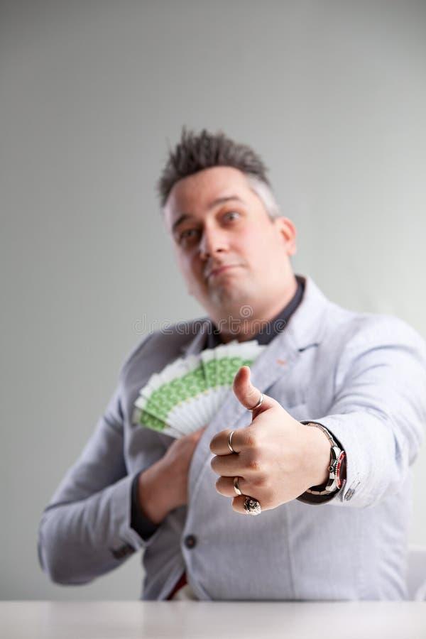 Hombre que embolsa un puñado de 100 notas euro fotos de archivo libres de regalías