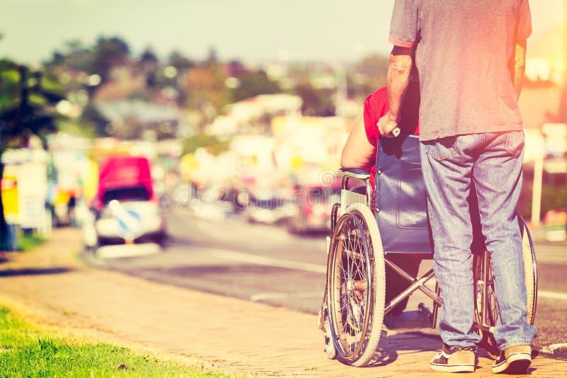 Hombre que empuja el sillón de ruedas fotos de archivo libres de regalías