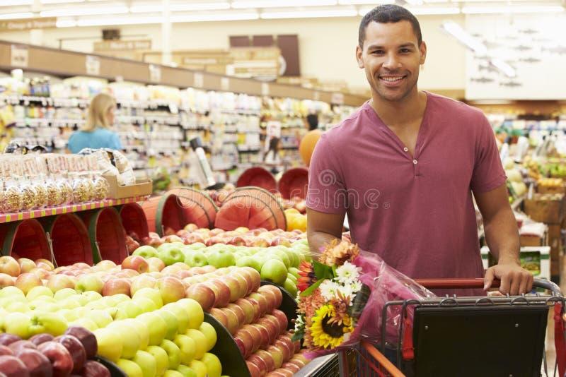 Hombre que empuja la carretilla por el contador de la fruta en supermercado imagen de archivo libre de regalías