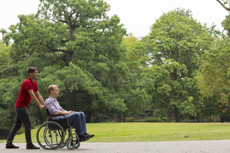Hombre que empuja a la persona discapacitada en la silla de ruedas imagenes de archivo