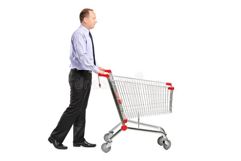 Hombre que empuja un carro de compras vacío foto de archivo