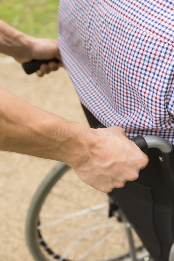 Hombre que empuja a una persona discapacitada en la silla de ruedas imagenes de archivo