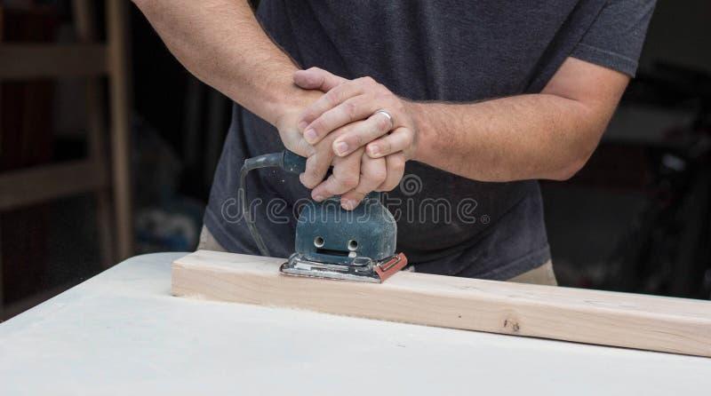 Hombre que enarena un proyecto de DIY imagen de archivo