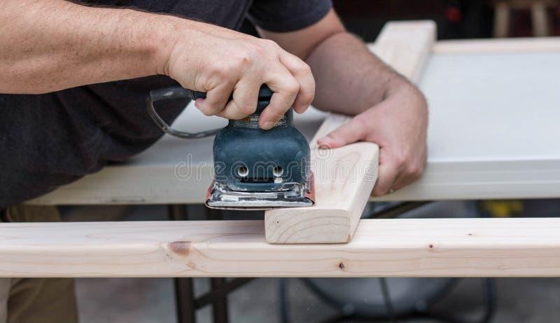 Hombre que enarena un proyecto de DIY fotografía de archivo