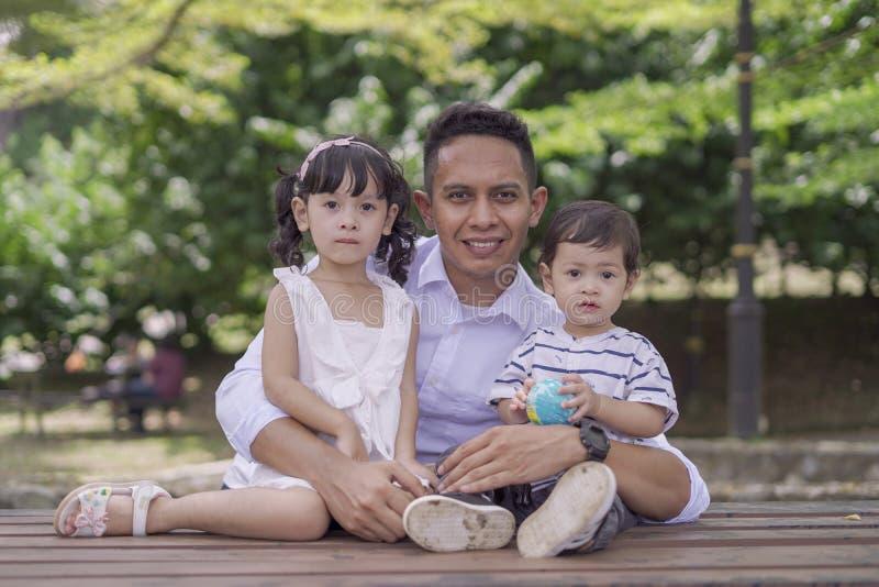 Hombre que enseña a sus niños a ahorrar el dinero en la hucha foto de archivo libre de regalías