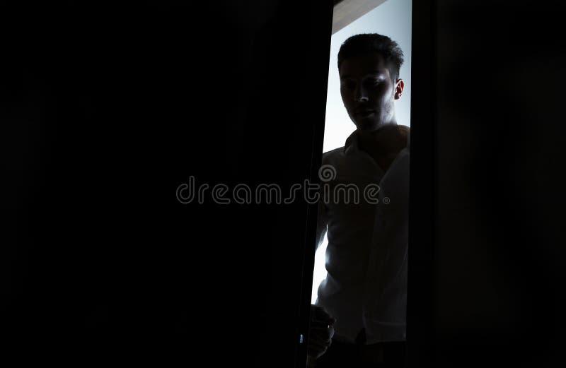Hombre que entra en un cuarto oscuro imagen de archivo libre de regalías