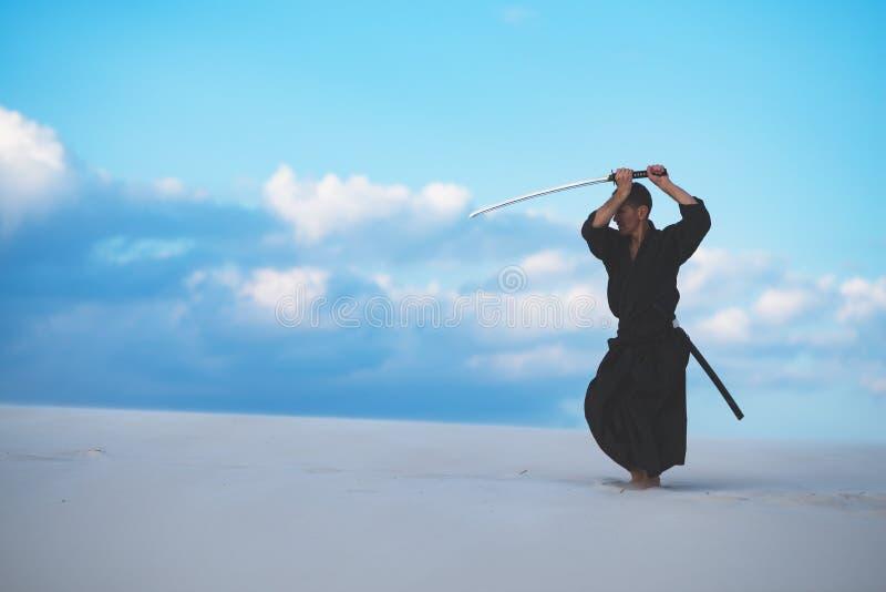 Hombre que entrena a artes marciales en desierto imágenes de archivo libres de regalías