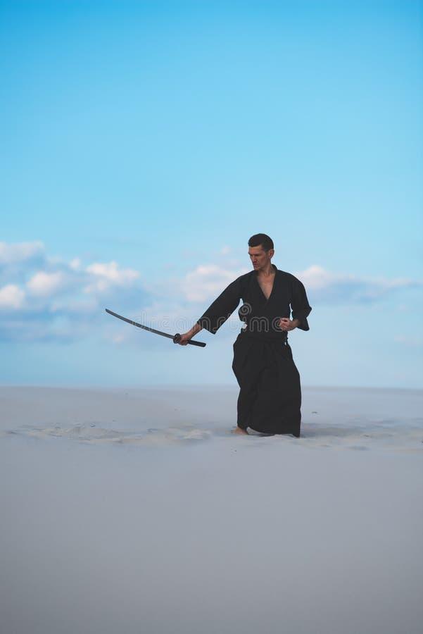Hombre que entrena a artes marciales en desierto fotografía de archivo