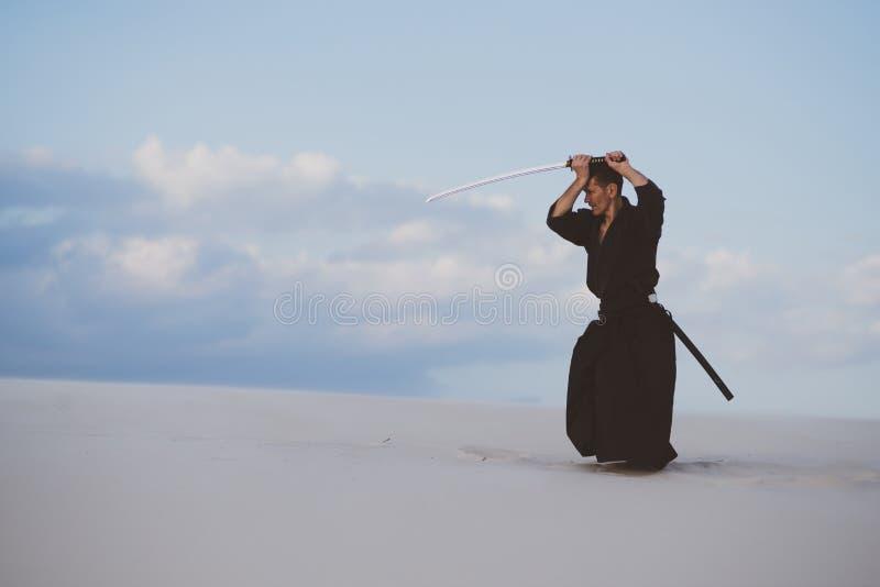Hombre que entrena a artes marciales en desierto imagen de archivo libre de regalías