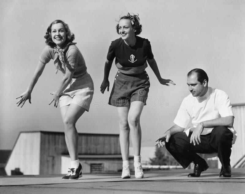 Hombre que entrena a dos bailarines de sexo femenino imágenes de archivo libres de regalías
