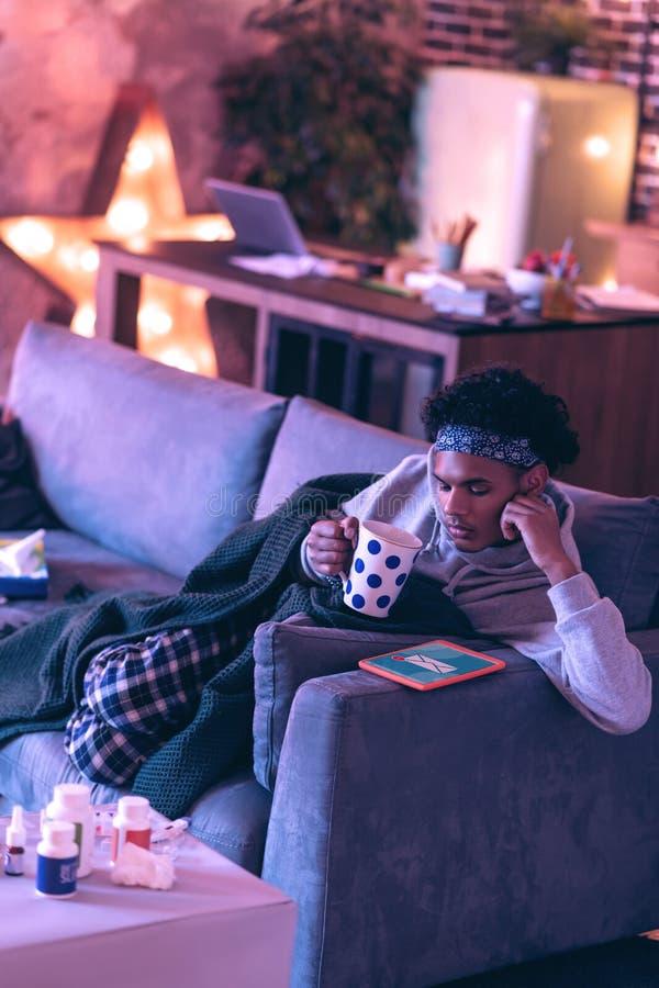 Hombre que envuelve en una tela escocesa, café de consumición y reflexionando sobre el mensaje imágenes de archivo libres de regalías