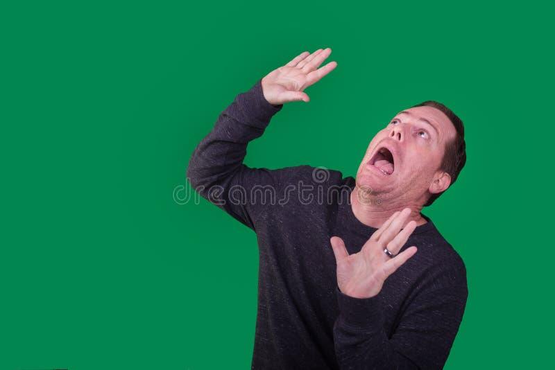 Hombre que es atacado o sorprendido por algo sobre él en fondo de pantalla verde foto de archivo libre de regalías