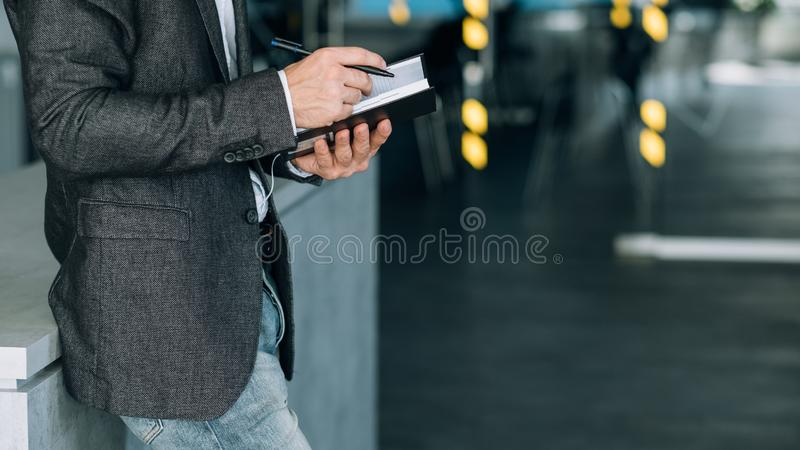 Hombre que escribe análisis de datos de los expedientes del cuaderno de la información fotos de archivo