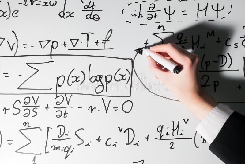 Hombre que escribe fórmulas complejas de la matemáticas en whiteboard Matemáticas y ciencia foto de archivo