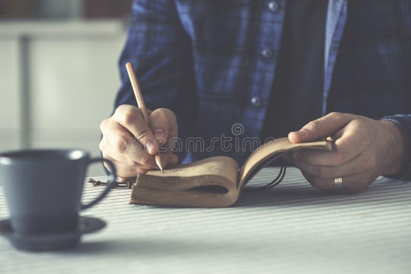 Hombre que escribe su cuaderno en la tabla fotos de archivo