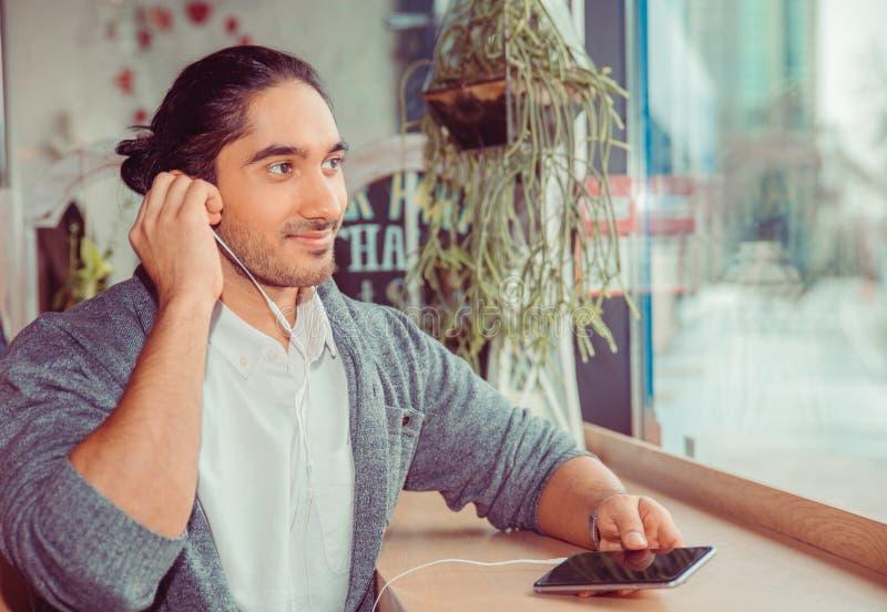 Hombre que escucha el libro audio cerca de una ventana en casa imagen de archivo