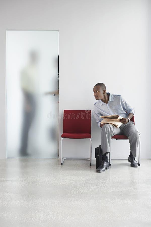 Hombre que escucha la charla de la gente detrás de la puerta translúcida fotografía de archivo libre de regalías