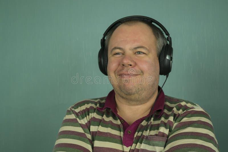 Hombre que escucha la música en los auriculares imagen de archivo