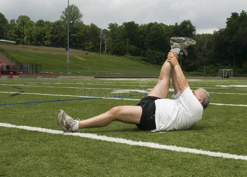 hombre que estira ejercitando el campo de deportes imagenes de archivo