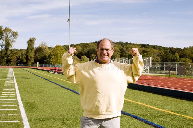 Hombre que estira ejercitando el campo de deportes fotografía de archivo libre de regalías