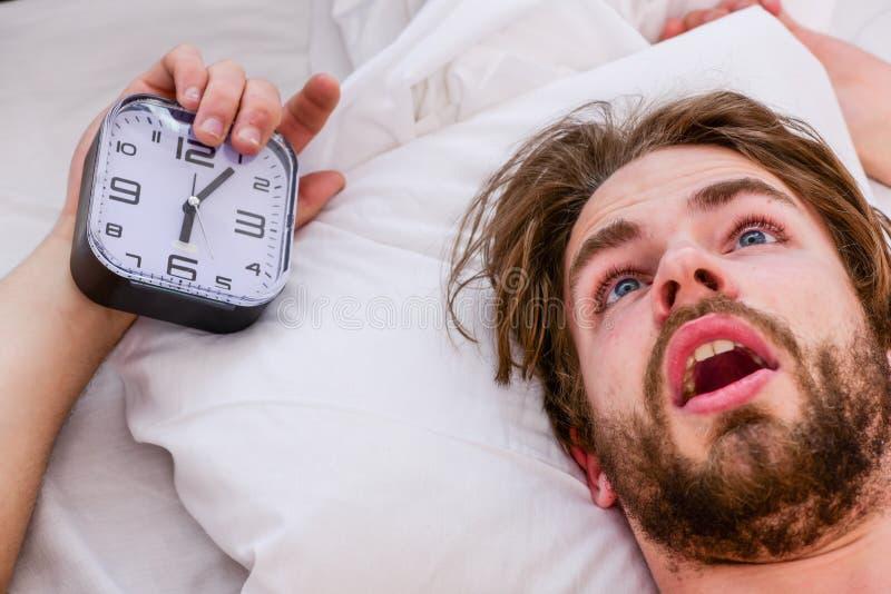 Hombre que estira en cama Estire después de despiertan por la mañana Hombre joven atractivo que se relaja en cama fotografía de archivo libre de regalías