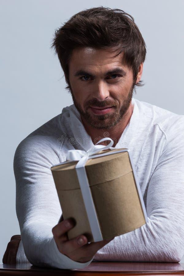 Hombre que estira hacia fuera una caja de regalo fotos de archivo libres de regalías