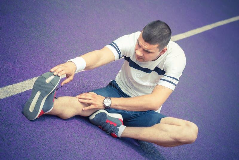 Hombre que estira la pierna en la pista corriente imagen de archivo libre de regalías