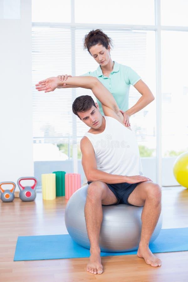 Hombre que estira su brazo con el instructor imagen de archivo libre de regalías