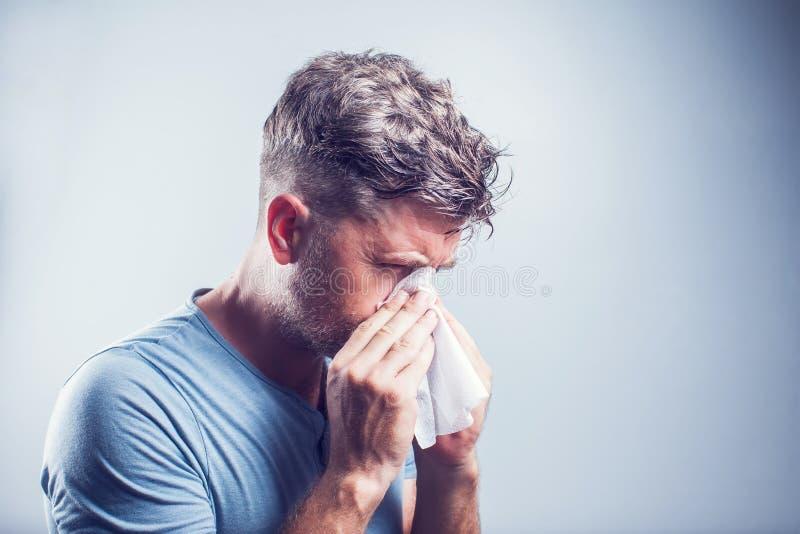 Hombre que estornuda en un tejido al aire libre Alergia del polen, primavera fotografía de archivo libre de regalías