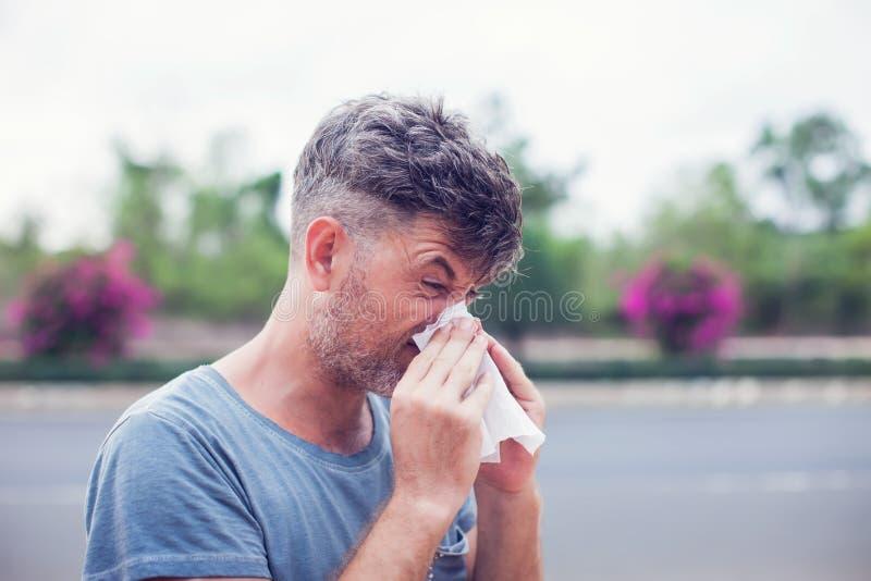 Hombre que estornuda en un tejido al aire libre Alergia del polen, primavera fotografía de archivo