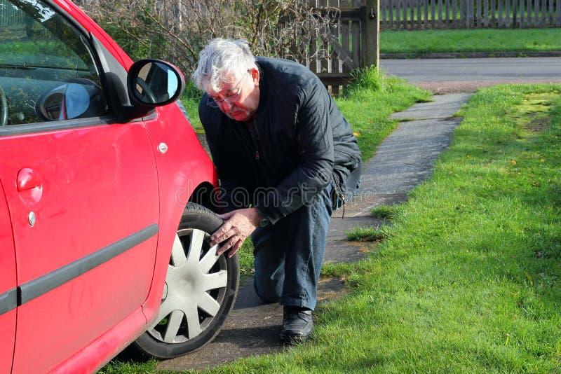 Hombre que examina los neumáticos o los neumáticos de coche. imagen de archivo